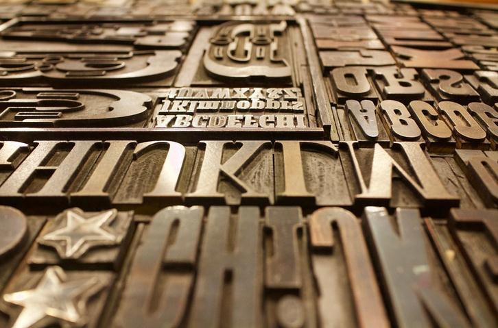 Image of different font letters on a wooden table